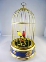 Éneklő madarak aranyozott kalitkában