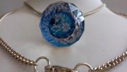 Fazettázott kristály gömb medál benne  színezett havasi gyopár díszítéssel hosszú láncon