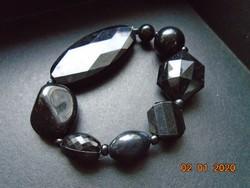 Különböző formájú és nagyságú fekete gyöngyökből karkötő