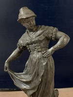 Nepviseletet viselő lányt ábrázoló szobrocska