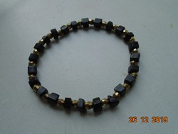 Szabálytalan fekete ásvány és Swarovski fazettált arany színű gyöngyökből,karkötő
