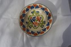 20 cm.-es patinás vajszínű fali kerámia dísztányér színes díszítéssel eladó.