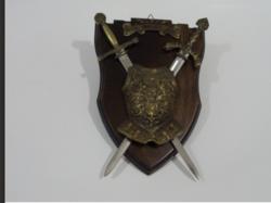 Két kard mini mellvérttel egy falitartón.