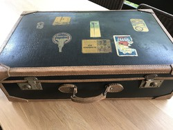 Antique leather suitcase with old hotel stickers on top